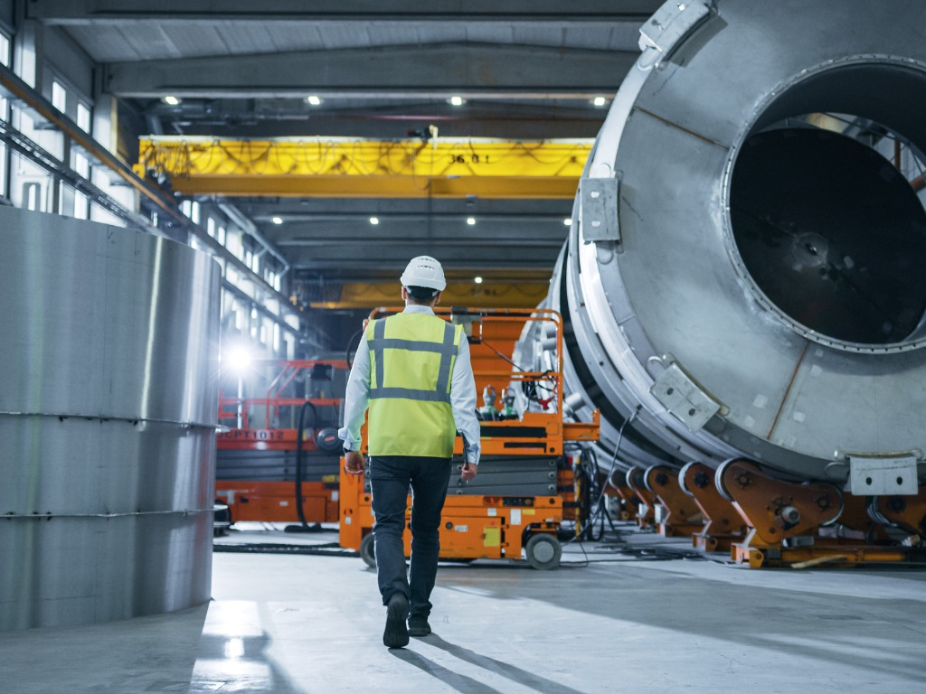 following shot of heavy industry engineers walking through factory picture id1224034141